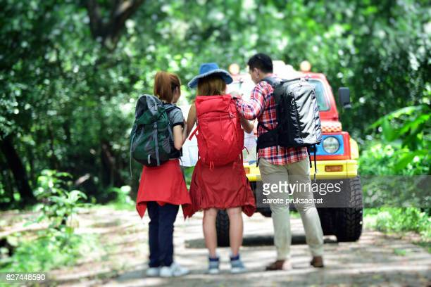 Group of young people hikers in forest with backpack .