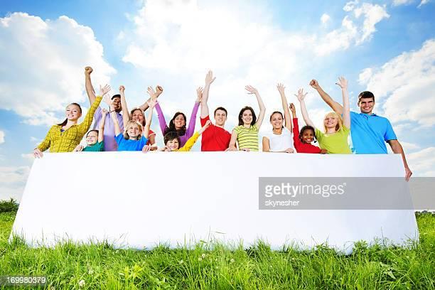 Grupo de jóvenes que sostiene una pizarra blanca