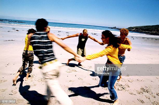 A group of young people holding hands and playing on the beach