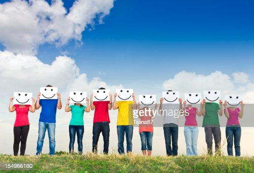 Group of young people holding papers with smileys : Stock Photo