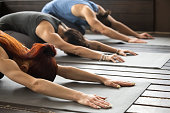 Group of young sporty afro american and caucasian people practicing yoga lesson stretching in Child exercise, Balasana pose, working out, indoor, studio close up. Healthy lifestyle concept