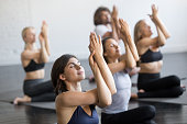 Group of young sporty people practicing yoga lesson, doing Cow Face exercise, Gomukasana pose, working out, indoor close up view, students training in club, studio