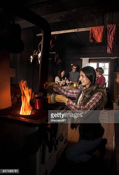 Group of young people in mountain hut with oven
