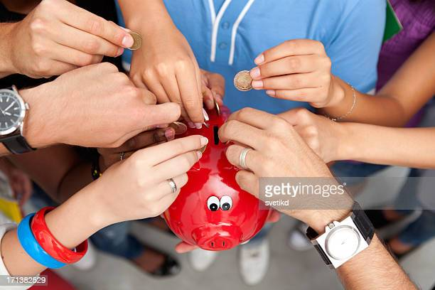 Group of young people inserting coins to a piggy bank.