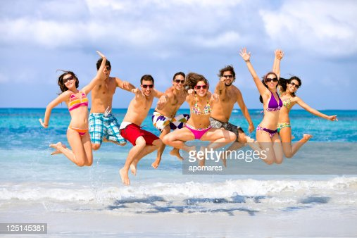 Happy group of young people jumping on a beach : Stock Photo