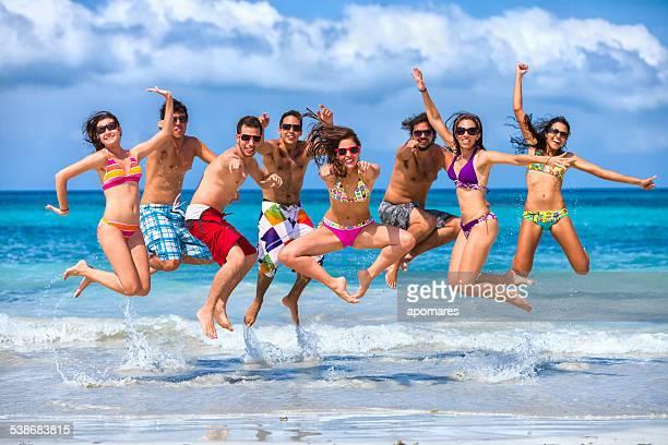 Groupe de jeunes de sauter sur la plage. Les vacances de printemps.