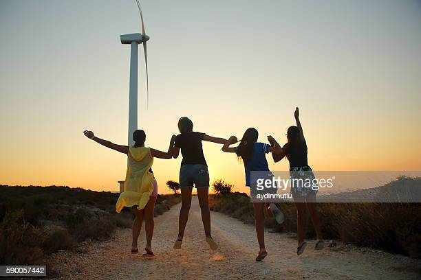 Group of young people jumping on Wind Turbine
