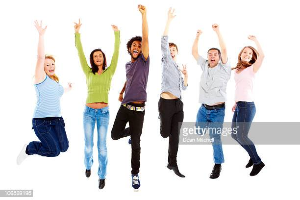 group of young people jumping over white