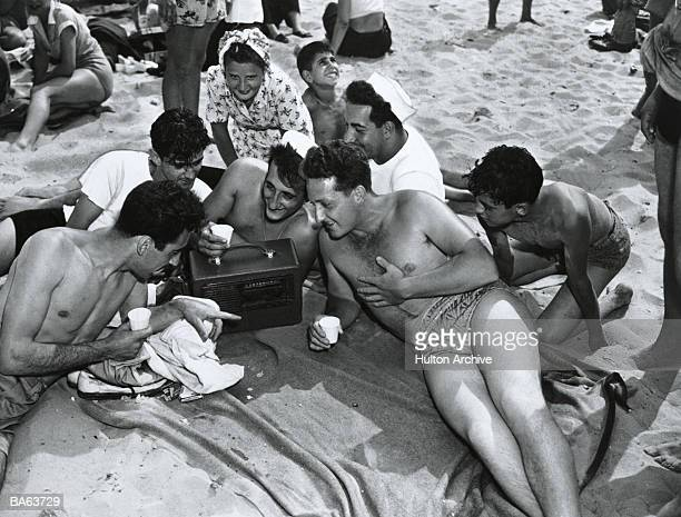 Group of young people listening to radio at the beach (B&W)