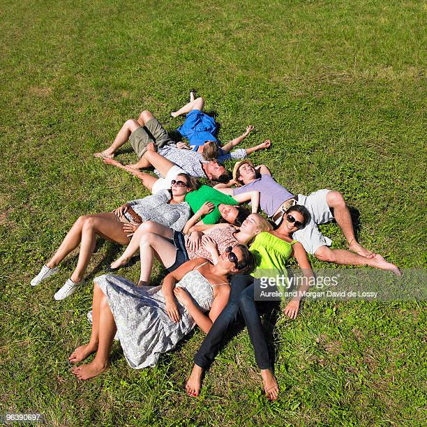 group of young people lying in field