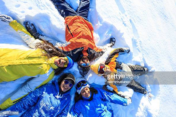 Group of young people making snow angels