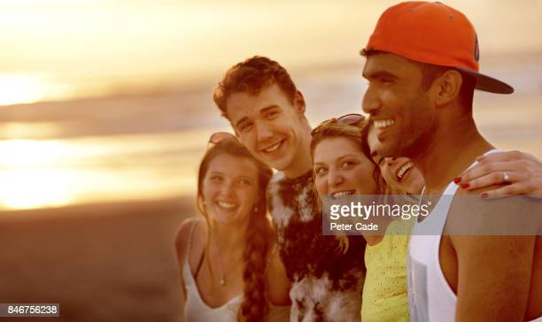 Group of young people on beach arms around each other