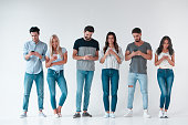Group of young people isolated on white background. Attractive youth standing together with smart phones in hands. Technology concept.