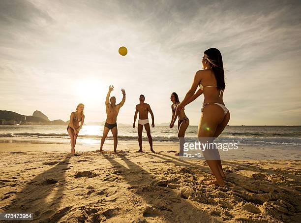 Group of young people playing beach volleyball at sunset.