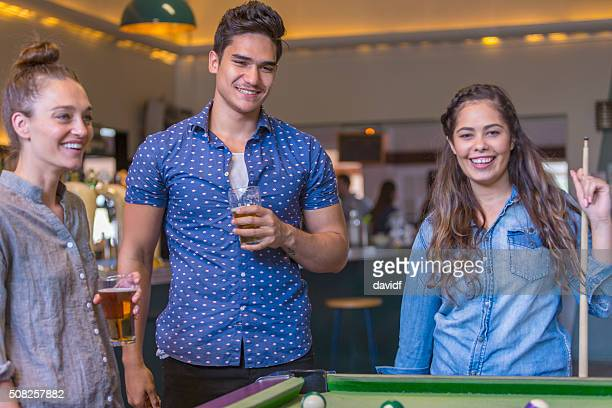 Group of Young People Playing Pool in a Bar