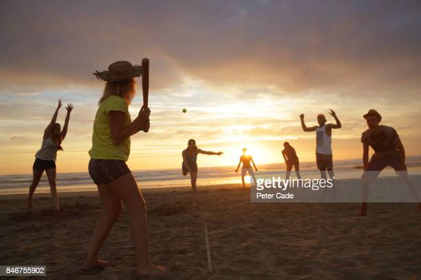 Group of young people playing rounders on beach at sunset
