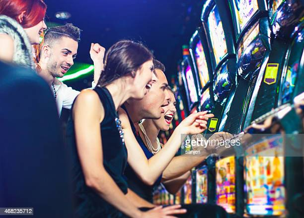 Group of young people playing slot machines at the Casino
