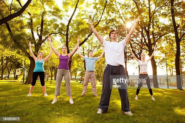 Gruppo di giovani praticare Tai Chi all'aperto