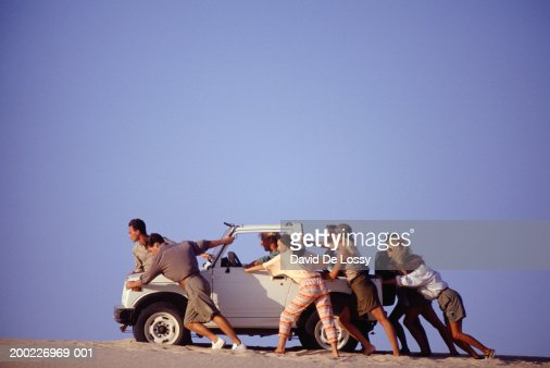 Group of young people pushing broken down car across sand, side view