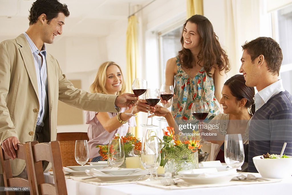 Group of young people raising glasses at dinner table, smiling : Stock Photo