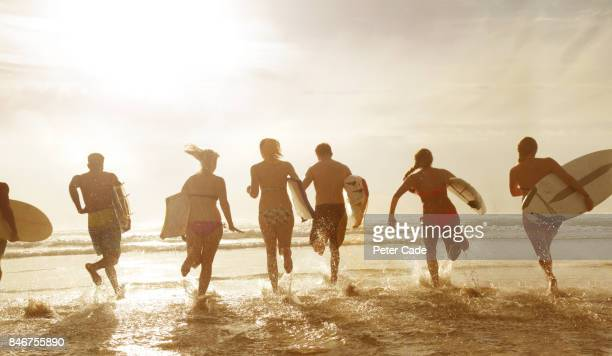 Group of young people running into the sea with boards