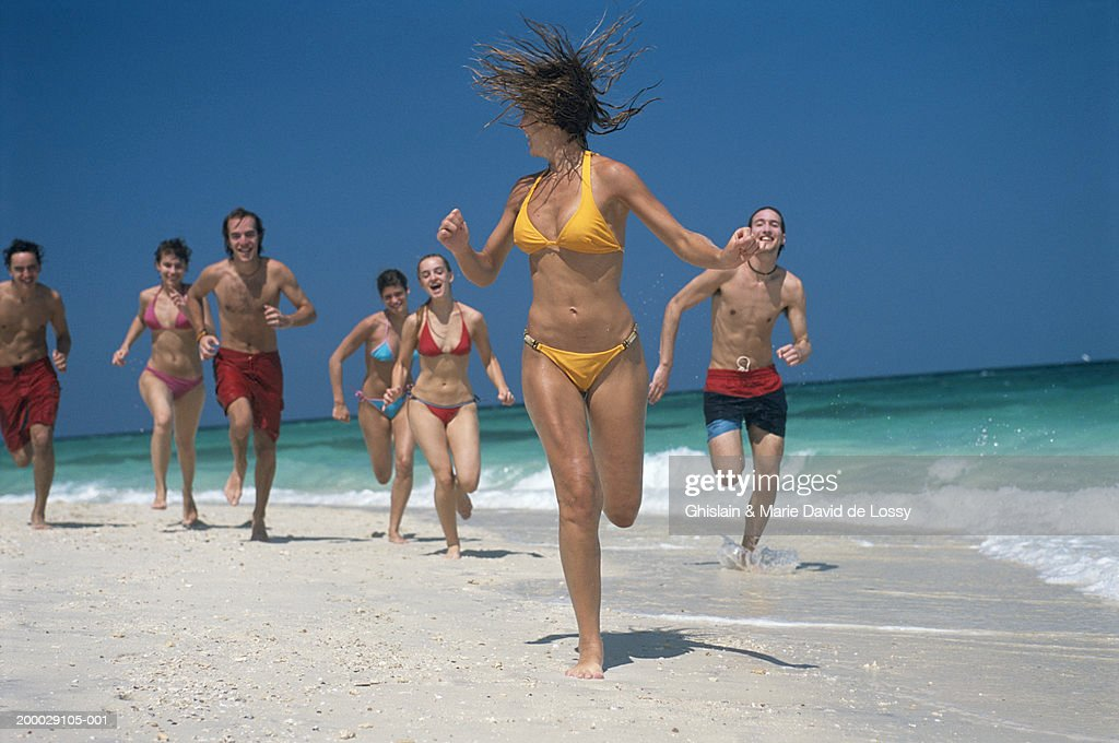Group of young people running on beach