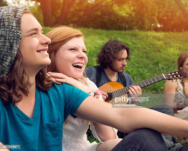Groupe de jeunes chantant et jouant de la guitare dans le parc.