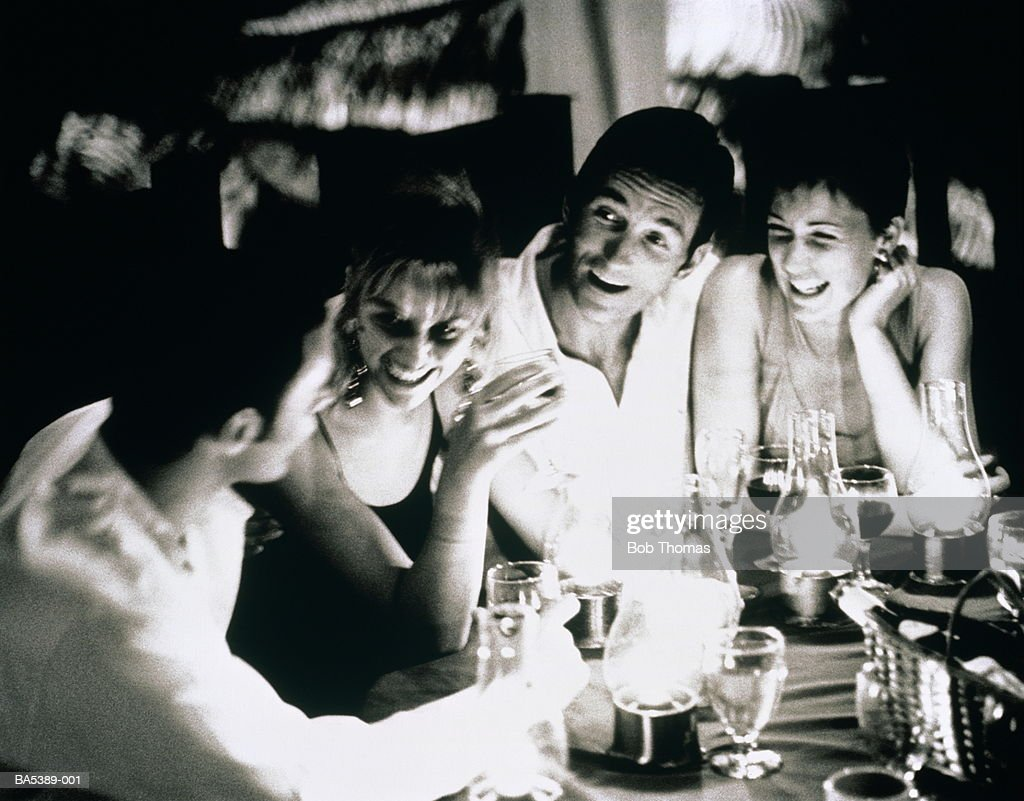 Group of young people sitting at restaurant table laughing (B&W) : Stock Photo
