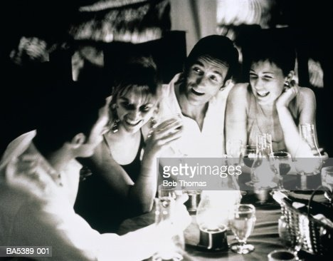 Group of young people sitting at restaurant table laughing (B&W) : Foto de stock