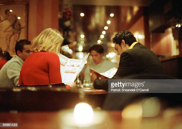 Group of young people sitting in restaurant looking at menus