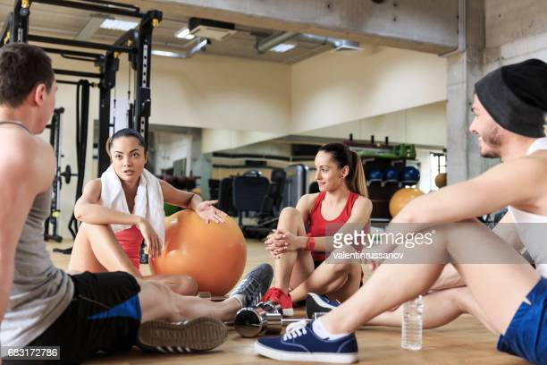 Group of young people sitting on floor in gym