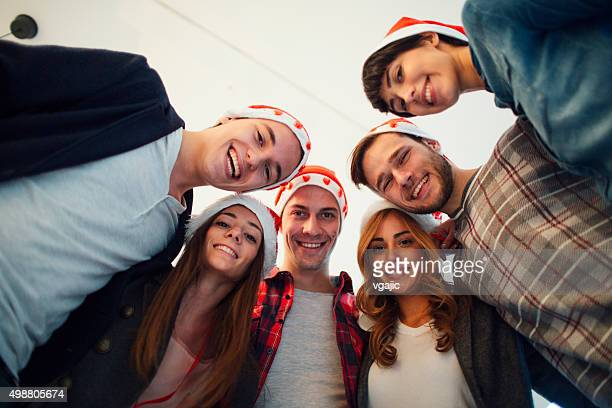 Group Of Young People Smiling With Santa Claus Hats.