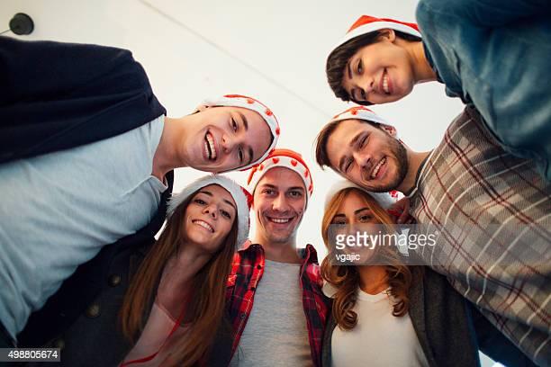 Groupe de jeunes souriant avec père Noël et chapeaux.