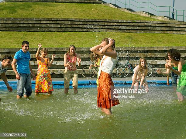 Group of young people splashing in pond