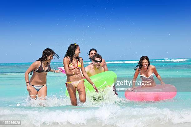 Groupe de jeunes de vous baigner dans les eaux turquoise de l'île tropicale de plage
