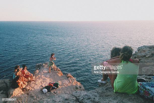 Group of young people staring at the sunset in Cap Barbaria Formentera Spain