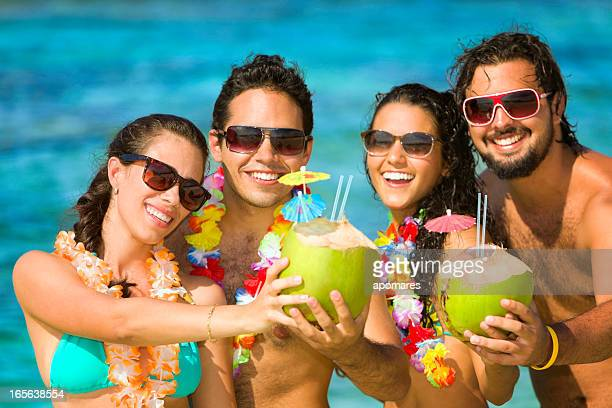 Group of young people toasting in a tropical turquoise beach