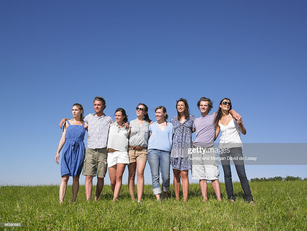group of young people walking in field : Stock Photo