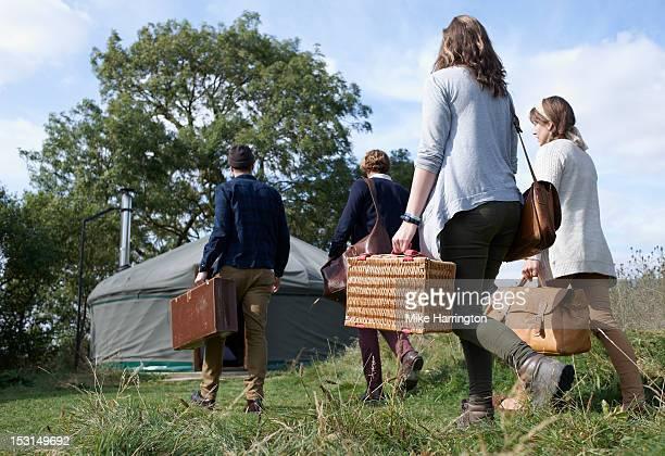 Group of young people walking towards yurt.
