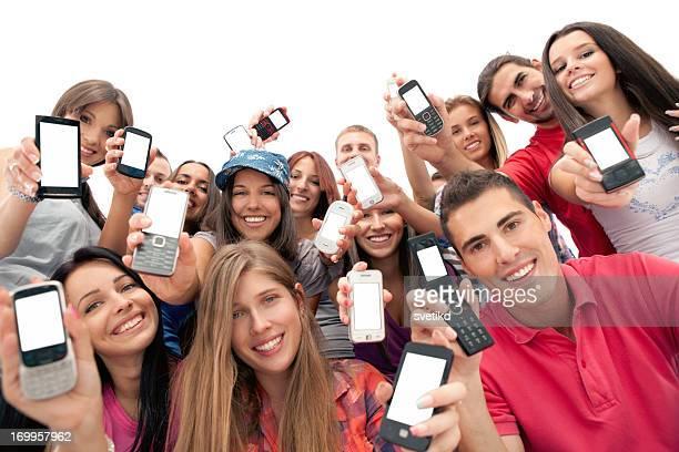 Groupe de jeunes gens avec les téléphones mobiles.
