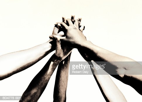 Group of young people's hands clasped together (toned B&W)