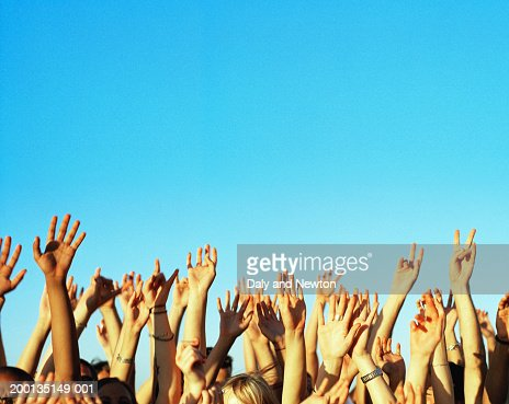 Group of young people's hands raised, outdoors