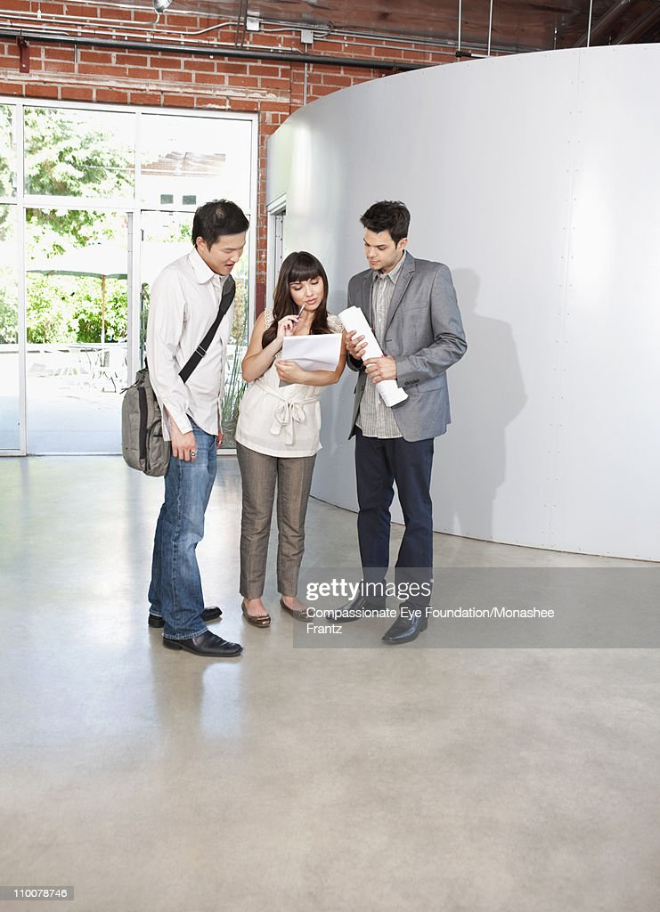 Group of young professionals looking at papers. : Stock Photo