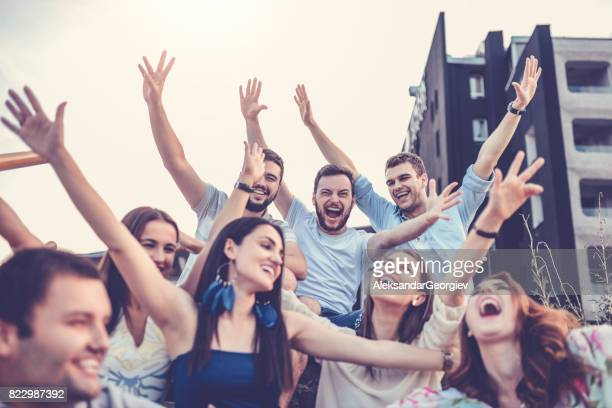 Group of Young Smiling People with Raised Hands Outdoors