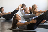 Group of young sporty people practicing fitness lesson with instructor, doing warming up exercise, boat pose, working out, students training in club, friends at fitness lesson, indoor, studio