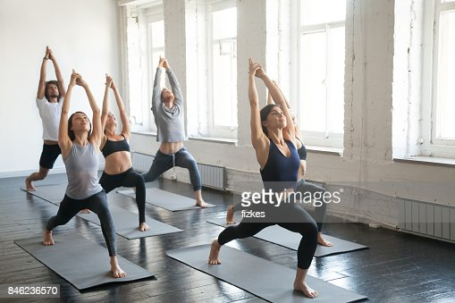 Group of young sporty people in Warrior one pose, studio : Stock Photo