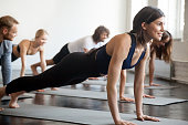 Group of young attractive sporty people practicing yoga lesson with instructor, doing Push ups or press ups exercise, standing in Plank pose, friends working out in club, indoor full length, studio