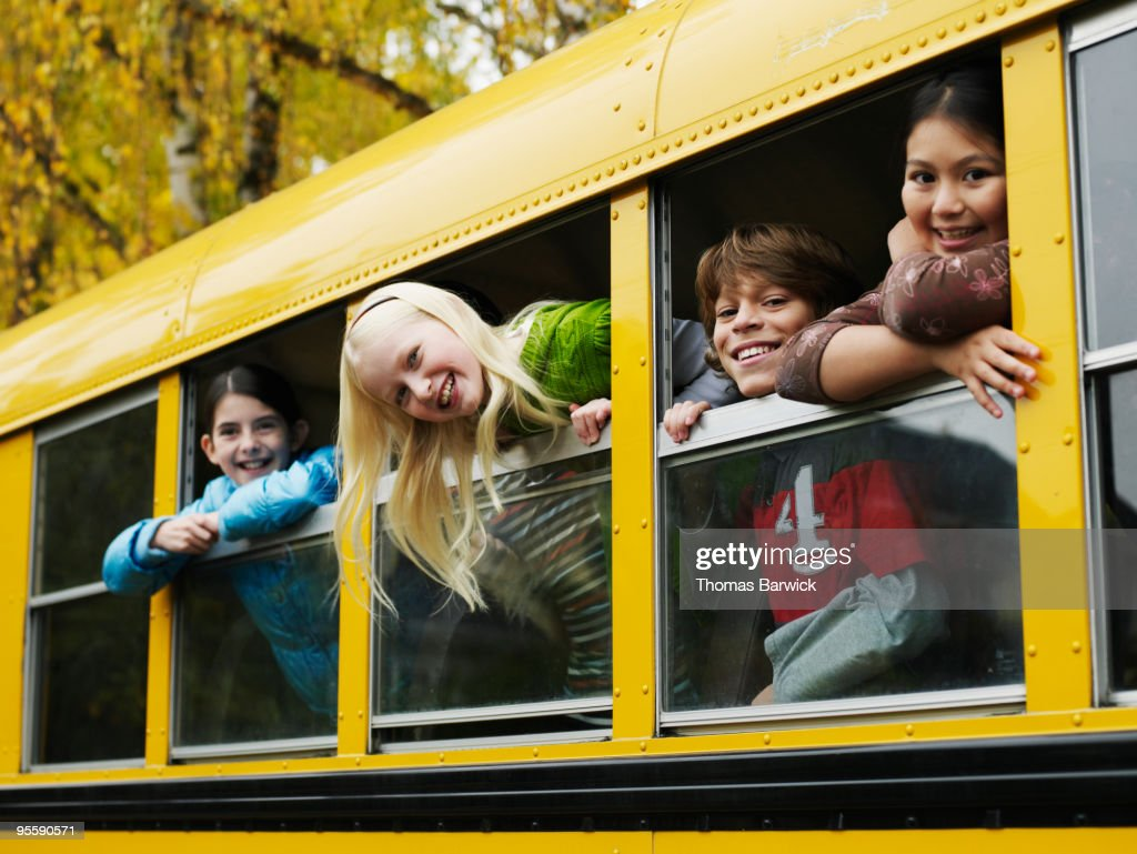 Group of young students hanging out bus windows