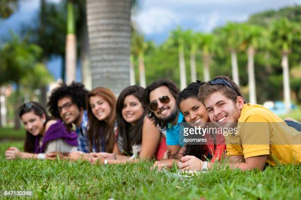 Group of young students relaxing together on campus grass