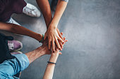 Cropped image of young people's hands on top of each other. Top view of young group with hands on stack.